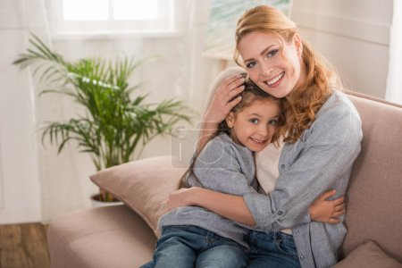happy mother and daughter hugging and smiling at camera together at home