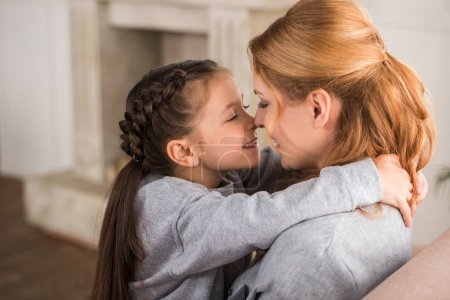 beautiful happy mother and daughter hugging together at home