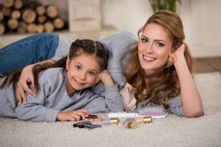 happy mother and daughter lying on carpet with cosmetics and smiling at camera