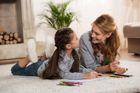 Photo for Happy mother and little daughter drawing with colored pencils and smiling each other at home - Royalty Free Image