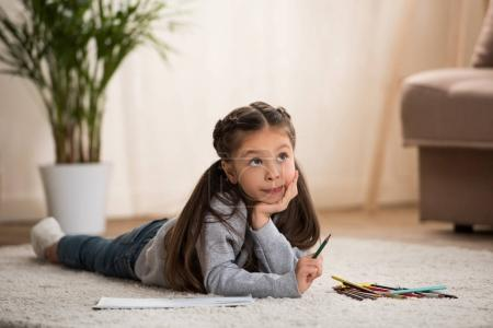adorable little child lying on carpet and drawing with colored pencils