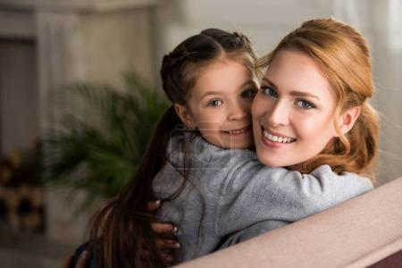 beautiful happy mother and daughter hugging and smiling at camera at home