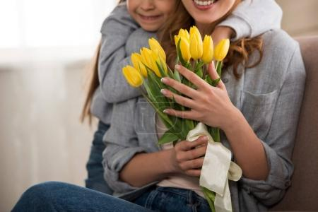 cropped shot of happy child hugging smiling mother with yellow tulips