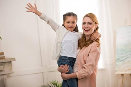 young woman carrying adorable little daughter and smiling at camera at home