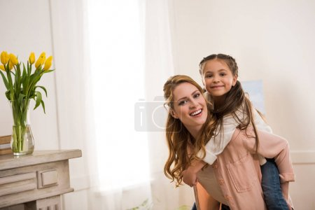 beautiful happy mother and daughter piggybacking and smiling at camera