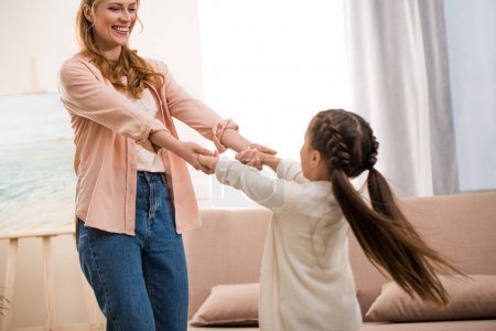 Photo for Beautiful happy mother and daughter holding hands and smiling each other at home - Royalty Free Image