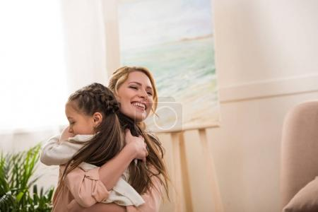 beautiful happy mother and daughter hugging at home