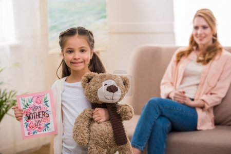 adorable child holding teddy bear and happy mothers day greeting card while mother sitting behind