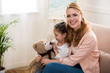 happy young woman smiling at camera while daughter playing with teddy bear