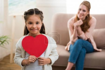 Photo for Adorable child holding red heart symbol and smiling at camera while mother sitting behind - Royalty Free Image
