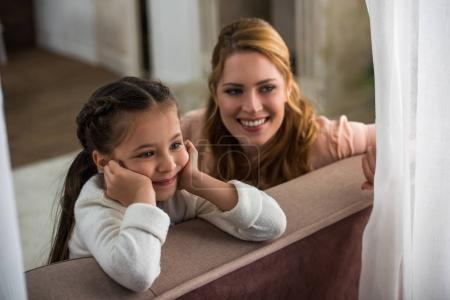 beautiful happy mother and daughter smiling and looking away at home