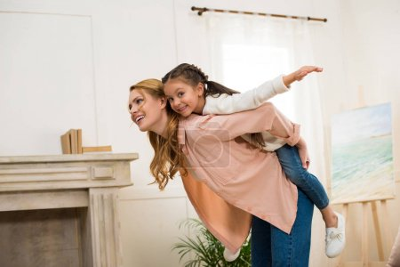 happy mother piggybacking adorable little daughter at home