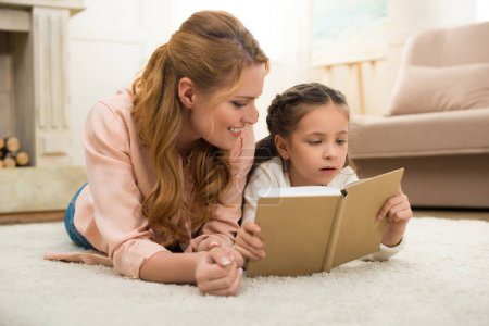happy mother and daughter lying on carpet and reading book together