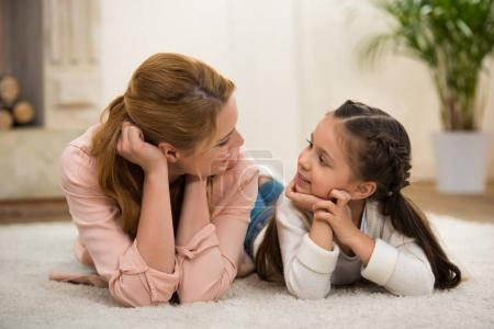Photo for Beautiful happy mother and daughter lying on carpet and looking at each other - Royalty Free Image