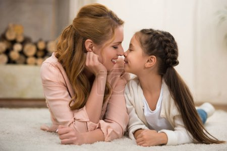 beautiful happy mother and daughter lying together on carpet