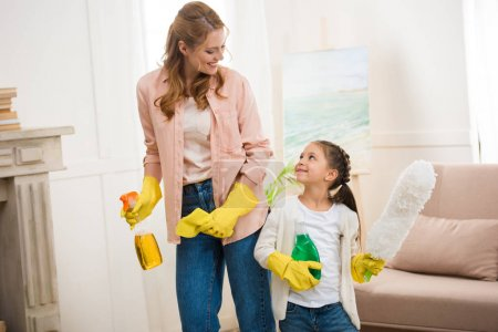 Photo for Happy mother and daughter cleaning room and smiling each other - Royalty Free Image