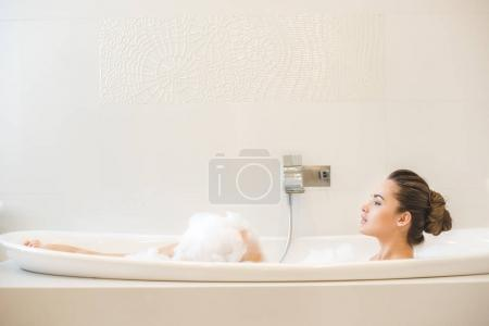 side view of young beautiful woman taking bath at home