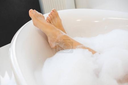 Photo pour Plan recadré de jambes féminines dans le bain avec de la mousse - image libre de droit