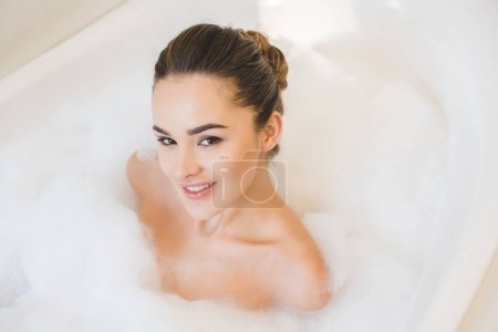 smiling young woman taking bath with foam at home