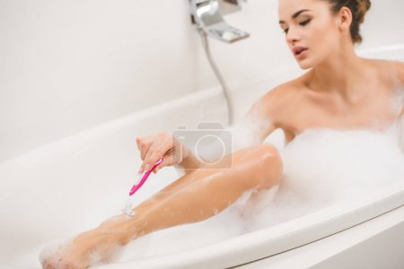 young woman shaving legs while taking bath at home