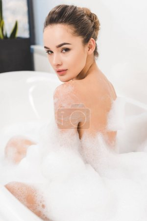 side view of beautiful young woman taking bath at home