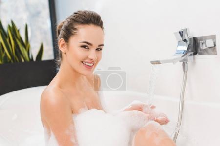 Photo pour Souriant jeune femme prenant un bain à la maison - image libre de droit