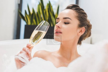 portrait of beautiful woman with glass of champagne taking bath