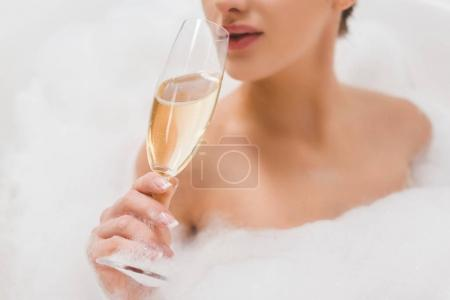 partial view of beautiful woman with glass of champagne taking bath