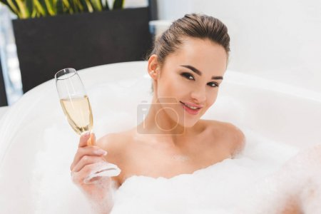 beautiful woman with glass of champagne taking bath