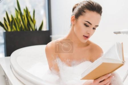 portrait of young woman reading book while taking bath