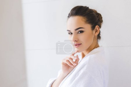 side view of beautiful young woman in bathrobe at home