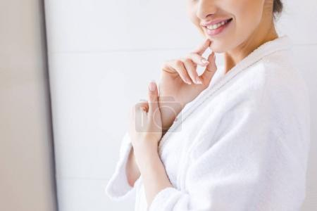cropped shot of smiling woman in bathrobe at home