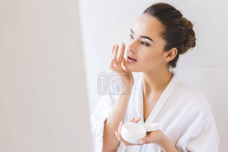Photo for Portrait of beautiful woman in bathrobe applying face cream - Royalty Free Image