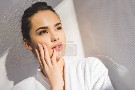 portrait of beautiful pensive woman in bathrobe at home