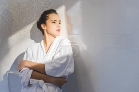portrait of beautiful pensive woman in bathrobe looking away at home
