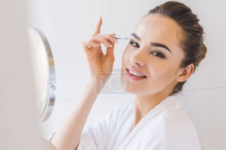 Photo for Young woman plucking eyebrows with tweezers - Royalty Free Image