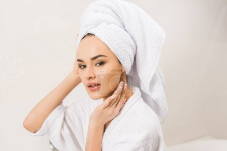 portrait of beautiful young woman in bathrobe with towel on head at home