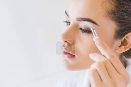 young woman plucking eyebrows with tweezers