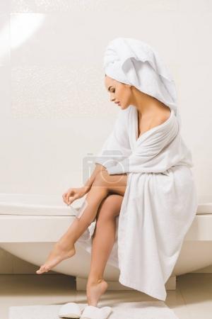Photo pour Vue latérale de la jeune femme en peignoir faisant épilation à la cire à la maison - image libre de droit