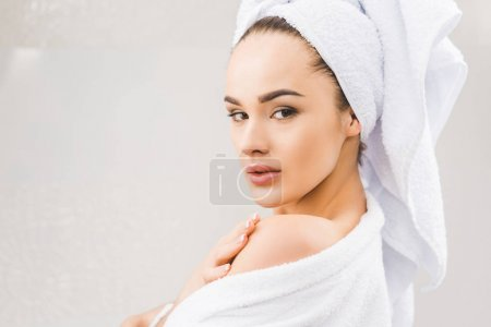 side view of beautiful young woman in bathrobe with towel on head at home