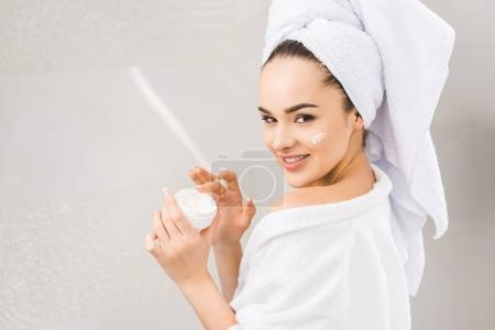 side view of smiling beautiful woman in bathrobe with towel on head holding face cream
