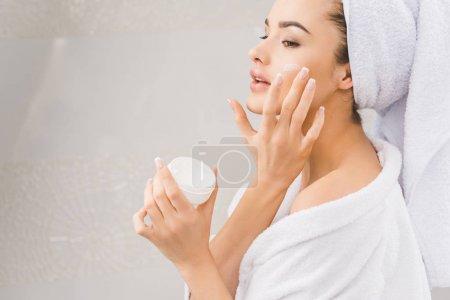 Photo pour Belle femme en peignoir avec serviette sur la tête appliquant crème visage - image libre de droit