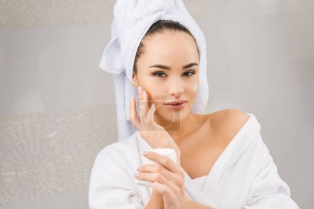 portrait of beautiful woman with towel on head holding face cream