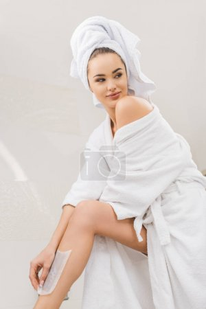 beautiful woman in bathrobe with towel on head doing wax depilation at home