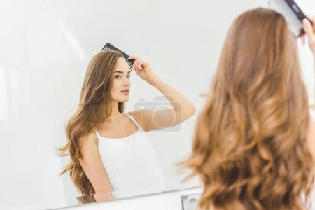 Photo pour Belle femme se brosser les cheveux avec un peigne dans salle de bain - image libre de droit