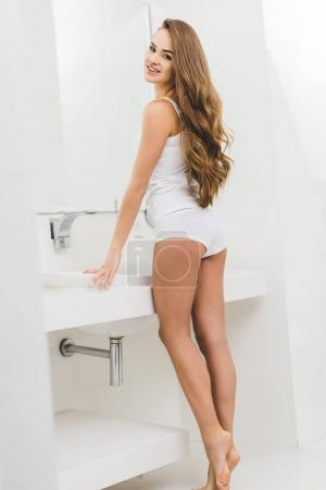 beautiful young woman leaning on sink in bathroom at home