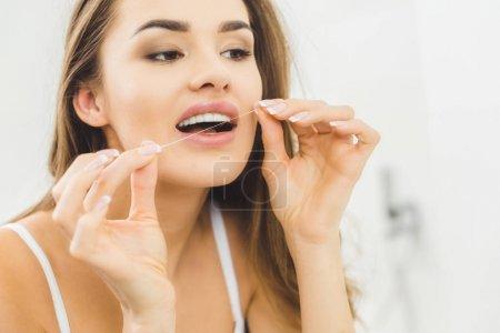 Photo pour Portrait de belle femme nettoyer les dents avec de la soie dentaire - image libre de droit