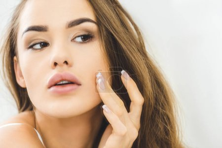 portrait of beautiful young woman checking skin