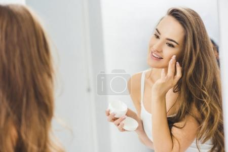 mirror reflection of beautiful smiling woman applying face cream