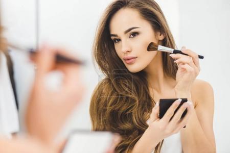 Photo pour Miroir reflet de belle jeune femme appliquant maquillage - image libre de droit